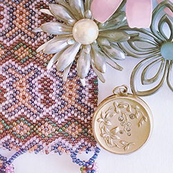 Beading in lavenders, pinks and blues, silver floral broaches and a burnished gold locket with floral detail.